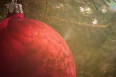 Υπόβαθρο Χριστουγέννων με ένα κόκκινο μπιχλιμπίδι και το χριστουγεννιάτικο δέντρο πίσω από το στοκ φωτογραφία