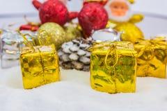 Υπόβαθρο Χριστουγέννων με ένα χρυσό κιβώτιο δώρων στο χιόνι στοκ φωτογραφίες