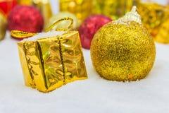 Υπόβαθρο Χριστουγέννων με ένα χρυσό κιβώτιο δώρων στο χιόνι στοκ εικόνες