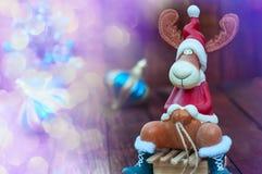 Υπόβαθρο Χριστουγέννων με μια άλκη παιχνιδιών στο ξύλινο έλκηθρο Στοκ Φωτογραφίες