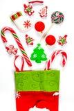 Υπόβαθρο Χριστουγέννων με μια κάλτσα από την οποία διεσπαρμένα δώρα, καραμέλα, νέα παιχνίδια διακοσμήσεων έτους σε ένα άσπρο υπόβ Στοκ Εικόνα