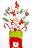 Υπόβαθρο Χριστουγέννων με μια κάλτσα από την οποία διεσπαρμένα δώρα, καραμέλα, νέα παιχνίδια διακοσμήσεων έτους σε ένα άσπρο υπόβ Στοκ φωτογραφία με δικαίωμα ελεύθερης χρήσης