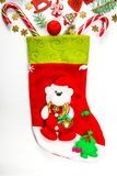 Υπόβαθρο Χριστουγέννων με μια κάλτσα από την οποία διεσπαρμένα δώρα, καραμέλα, νέα παιχνίδια διακοσμήσεων έτους σε ένα άσπρο υπόβ Στοκ εικόνες με δικαίωμα ελεύθερης χρήσης