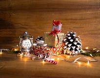 Υπόβαθρο Χριστουγέννων με μια κόκκινη διακόσμηση, ένα χρυσό κιβώτιο δώρων, τα μούρα και το έλατο στο χιόνι Στοκ Εικόνες