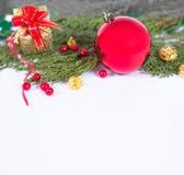 Υπόβαθρο Χριστουγέννων με μια κόκκινη διακόσμηση, ένα χρυσό κιβώτιο δώρων, τα μούρα και το έλατο στο χιόνι Στοκ φωτογραφία με δικαίωμα ελεύθερης χρήσης