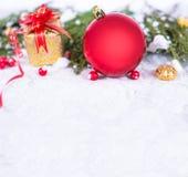 Υπόβαθρο Χριστουγέννων με μια κόκκινη διακόσμηση, ένα χρυσό κιβώτιο δώρων, τα μούρα και το έλατο στο χιόνι Στοκ Εικόνα