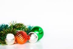 Υπόβαθρο Χριστουγέννων με μια κόκκινη διακόσμηση, την πράσινη διακόσμηση και την ασημένια διακόσμηση στο άσπρο υπόβαθρο Στοκ Εικόνες