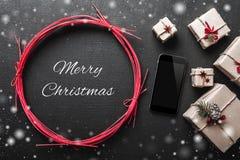 Υπόβαθρο Χριστουγέννων με τα δώρα και κινητό τηλεφωνικό διάστημα με το χιονίζοντας μήνυμα Χριστουγέννων Στοκ εικόνα με δικαίωμα ελεύθερης χρήσης