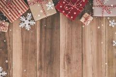 Υπόβαθρο Χριστουγέννων με τα κιβώτια δώρων και snowflake διακόσμηση σε έναν ξύλινο πίνακα Στοκ Εικόνες