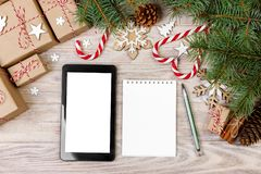 Υπόβαθρο Χριστουγέννων με τα κιβώτια δώρων, ταμπλέτα με την άσπρη οθόνη και κενό σημειωματάριο, διάστημα αντιγράφων Πρότυπο για τ Στοκ φωτογραφίες με δικαίωμα ελεύθερης χρήσης