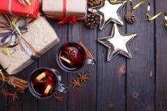 Υπόβαθρο Χριστουγέννων με τα κιβώτια δώρων, το θερμαμένες κρασί και τη διακόσμηση Στοκ Εικόνες
