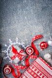Υπόβαθρο Χριστουγέννων με τα κιβώτια δώρων, τις κορδέλλες, snowflakes εγγράφου και τις κόκκινες διακοσμήσεις Στοκ Εικόνα