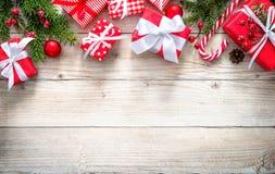 Υπόβαθρο Χριστουγέννων με τα κόκκινα κιβώτια δώρων στον ξύλινο πίνακα Στοκ Εικόνες