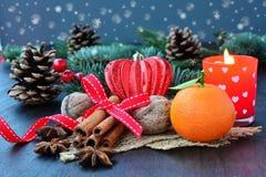 Υπόβαθρο Χριστουγέννων με τα φρούτα, τα καρυκεύματα, το έλατο και το κερί Στοκ Εικόνα