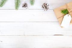 Υπόβαθρο Χριστουγέννων με τα χειροποίητα παρόντα κιβώτια δώρων και αγροτική διακόσμηση στο λευκό ξύλινο πίνακα Στοκ Φωτογραφία