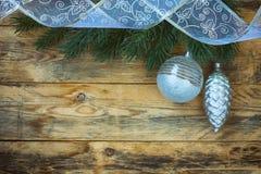 Υπόβαθρο Χριστουγέννων με την ασημένια σφαίρα, κώνοι, κορδέλλες, δέντρο γουνών Στοκ φωτογραφία με δικαίωμα ελεύθερης χρήσης