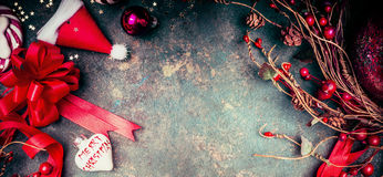 Υπόβαθρο Χριστουγέννων με την κόκκινη διακόσμηση διακοπών, την καρδιά Χαρούμενα Χριστούγεννας, το στεφάνι μούρων και το καπέλο Sa Στοκ Εικόνες