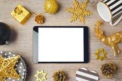 Υπόβαθρο Χριστουγέννων με την ψηφιακές ταμπλέτα και τις διακοσμήσεις επάνω από την όψη Στοκ Εικόνες