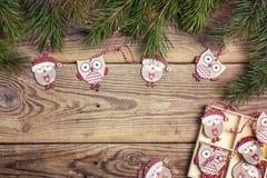 Υπόβαθρο Χριστουγέννων με τις αστείους κουκουβάγιες και τους κλάδους πεύκων στο παλαιό wo Στοκ Εικόνες