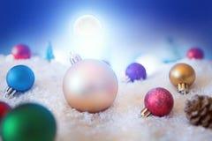 Υπόβαθρο Χριστουγέννων με τις σφαίρες Χριστουγέννων στο χιόνι πέρα από fir-tree, το νυχτερινό ουρανό και το φεγγάρι πεδίο βάθους  Στοκ Εικόνες