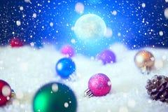 Υπόβαθρο Χριστουγέννων με τις σφαίρες Χριστουγέννων στο χιόνι πέρα από fir-tree, το νυχτερινό ουρανό και το φεγγάρι πεδίο βάθους  Στοκ εικόνα με δικαίωμα ελεύθερης χρήσης