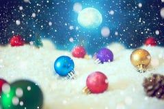 Υπόβαθρο Χριστουγέννων με τις σφαίρες Χριστουγέννων στο χιόνι πέρα από fir-tree, το νυχτερινό ουρανό και το φεγγάρι πεδίο βάθους  Στοκ Φωτογραφίες