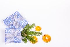 Υπόβαθρο Χριστουγέννων με τον κομψό κλάδο, το δώρο και ένα πορτοκάλι Λαμπρό κιβώτιο δώρων στο άσπρο υπόβαθρο στοκ φωτογραφία με δικαίωμα ελεύθερης χρήσης