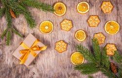 Υπόβαθρο Χριστουγέννων με τους κομψούς κλάδους, το κιβώτιο δώρων, τις πορτοκαλιές φέτες και τα σπιτικά μπισκότα υπό μορφή snowfla Στοκ εικόνα με δικαίωμα ελεύθερης χρήσης