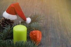 Υπόβαθρο Χριστουγέννων με το καπέλο και το κερί Santa στοκ εικόνα με δικαίωμα ελεύθερης χρήσης