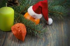 Υπόβαθρο Χριστουγέννων με το καπέλο και το κερί Santa στοκ φωτογραφία