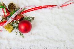 Υπόβαθρο Χριστουγέννων με το κόκκινα μπιχλιμπίδι, το χιόνι και snowflakes Στοκ φωτογραφία με δικαίωμα ελεύθερης χρήσης