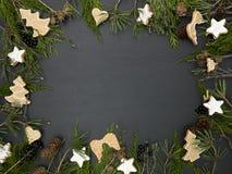 Υπόβαθρο Χριστουγέννων με το πλαίσιο και τα μπισκότα στοκ εικόνες