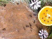 Υπόβαθρο Χριστουγέννων με το πορτοκάλι, τα γαρίφαλα, τα αστέρια και τους κλάδους έλατου Στοκ Εικόνες