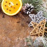 Υπόβαθρο Χριστουγέννων με το πορτοκάλι, τα γαρίφαλα, τα αστέρια και τους κλάδους έλατου Στοκ Φωτογραφίες