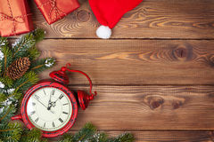 Υπόβαθρο Χριστουγέννων με το ρολόι, το δέντρο έλατου χιονιού και τα κιβώτια δώρων Στοκ Εικόνα