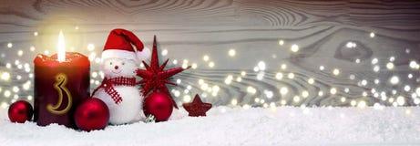 Υπόβαθρο Χριστουγέννων με το τρίτο κερί εμφάνισης και χιονάνθρωπος με την κόκκινη διακόσμηση στοκ εικόνα