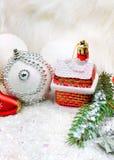 Υπόβαθρο Χριστουγέννων με το χιόνι, μπιχλιμπίδια Χριστουγέννων, κλαδίσκοι πεύκων Στοκ Φωτογραφίες