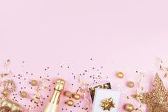 Υπόβαθρο Χριστουγέννων με το χρυσό δώρο ή παρούσες διακοσμήσεις κιβωτίων, σαμπάνιας και διακοπών στη ρόδινη άποψη επιτραπέζιων κο στοκ εικόνα με δικαίωμα ελεύθερης χρήσης