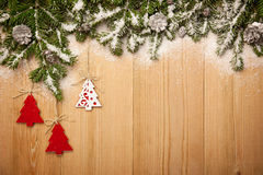 Υπόβαθρο Χριστουγέννων με firtree, τα διακοσμητικούς δέντρα και τους κώνους επάνω Στοκ Φωτογραφίες