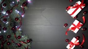 Υπόβαθρο Χριστουγέννων του μαύρου ξύλου που διακοσμείται με τους κλάδους έλατου Πεύκο που εξωραΐζεται με τα κόκκινα φω'τα κομφετί φιλμ μικρού μήκους