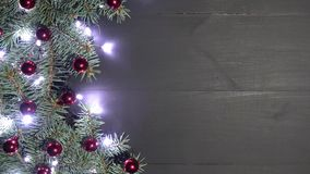 Υπόβαθρο Χριστουγέννων του μαύρου ξύλου που διακοσμείται με τους κλάδους έλατου Πεύκο που διακοσμείται με τα μπιχλιμπίδια και τα  φιλμ μικρού μήκους
