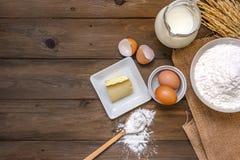 Υπόβαθρο ψησίματος με τα ακατέργαστα αυγά, το βούτυρο και το αλεύρι Στοκ Φωτογραφία