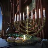 Υπόβαθρο Hanukkah με τα κεριά, donuts, τα περιστρεφόμενα τοπ και παλαιά βιβλία Στοκ Εικόνα