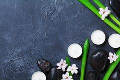 Υπόβαθρο SPA με το χαλίκι μασάζ, τα πράσινα φύλλα, τα λουλούδια και τα κεριά στο μαύρο πίνακα πετρών άνωθεν Aromatherapy, ομορφιά Στοκ φωτογραφία με δικαίωμα ελεύθερης χρήσης