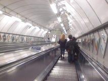 Υπόγειες κυλιόμενες σκάλες στην πόλη του Λονδίνου στην Αγγλία στην Ευρώπη με έναν επιβάτη τραίνα και μεταφορά των ανθρώπων στοκ εικόνες