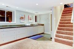 Υπόγειο με τη σκάλα, λευκά γραφεία για την αποθήκευση. Στοκ Φωτογραφία
