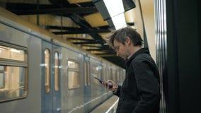 Υπόγειο περπάτημα υπογείων ατόμων χαμόγελου μπροστά από το τραίνο που μιλά με την εφαρμογή τηλεφωνικού smartphone τηλεφωνικών κυτ φιλμ μικρού μήκους