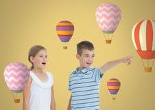 υπόδειξη παιδιών που εκπλήσσεται με το κενό υπόβαθρο δωματίων με τα μπαλόνια ζεστού αέρα ελεύθερη απεικόνιση δικαιώματος
