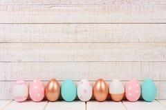 Υπόλοιπος κόσμος των αυγών Πάσχας στο άσπρο ξύλο Αυξήθηκε χρυσός, ρόδινος, τυρκουάζ και άσπρος Στοκ φωτογραφίες με δικαίωμα ελεύθερης χρήσης