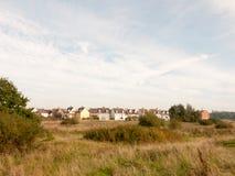 Υπόλοιπος κόσμος των σπιτιών στην άκρη ακτών πίσω από τον τομέα πέρα από τον ουρανό τρόπων και Στοκ Φωτογραφίες